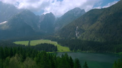 Aerial - Scenic landscape of the lake, mountains and vast spruce forest in sprin Stock Footage