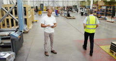 4K Young business manager in factory warehouse looking at tablet computer Stock Footage