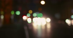 Night lights in city and reflections of carlight crossing on a road, vintage Stock Footage