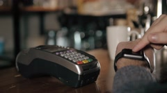 Customer paying with NFC technology by smart watch contactless on terminal in Stock Footage