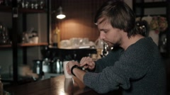 Young stylish and fashionable man checking his smartwatch in cafe bar and drink Stock Footage