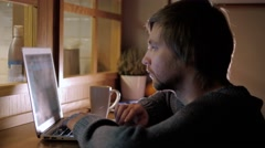 Young male freelancer chatting on mobile phone while sitting front open laptop Stock Footage