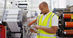 4K Business manager in a printing factory looking down at computer tablet  Stock Footage