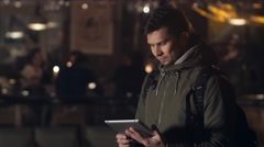 Handsome young man with tablet pc navigating in the night streets Stock Footage