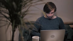 Young male freelancer sitting front open laptop computer working in natural food Stock Footage
