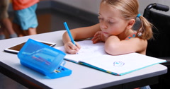 Disabled schoolgirl studying in classroom Stock Footage