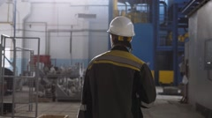 Worker wearing safety hat and uniform in a modern factory Stock Footage