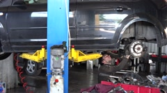 Mechanic working under lifted car. close up of tools. focus change Stock Footage