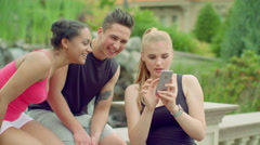 Cheerful friends having fun in park. Young people using phone outdoor at summer Stock Footage