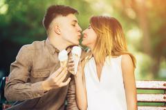 Man and woman sitting eating ice cream Kuvituskuvat