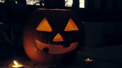 Candles Glow Around a Spooky Jack o'lantern Pumpkin Stock Footage