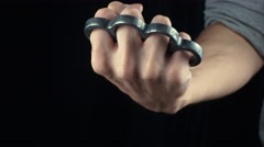 Placing knuckle-duster on the hand male fist with brass knuckles Stock Footage