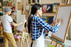 Young woman standing in front of easel and drawing on paper-sheet Stock Photos