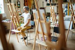 Skilled man learning to paint in art-school Stock Photos