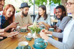 African-american guy looking at camera among his friends in cafe Stock Photos