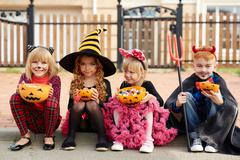 Row of kids with pumpkin bowls full of candies looking at camera Stock Photos
