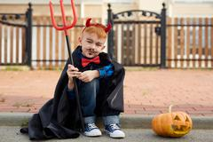 Devil boy with pitchfork looking at camera Stock Photos