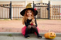 Witch girl in hat and curly wig looking at camera against fence Stock Photos
