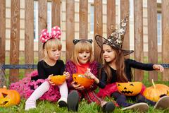 Little witch sharing tasty sweet with one of her friends Stock Photos