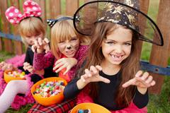 Halloween girl in witch hat showing frightening gesture Stock Photos