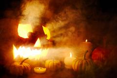 Scary jack-o-lantern surrounded by burning candles in the dark Stock Photos