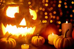 Halloween composition lit by burning candles and garlands Stock Photos