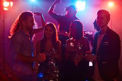 Happy young friends spending evening in night club Stock Photos