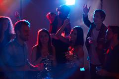 Group of dancers with cocktails enjoying party Stock Photos