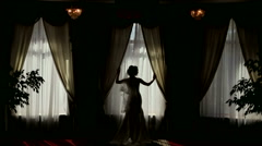 Silhouette of a beautiful bride near the window in the hotel. Stock Footage