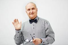 Elegant mature man waving hand and looking at camera Stock Photos