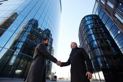 Entrepreneurs greeting one another against modern office buildings Stock Photos