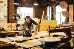 Young craftsman working with fretsaw and wooden board Stock Photos