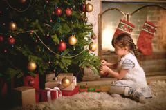 Cute child decorating xmas tree with bubbles Stock Photos