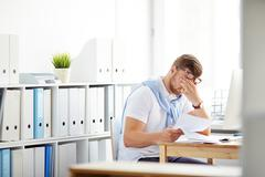 Tired accountant or banker with papers sitting at workplace Stock Photos