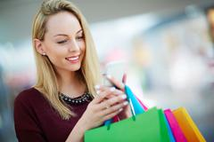Shopper with paperbags reading promo sms Stock Photos
