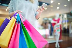 Paperbags held by mobile shopaholic with smartphone Stock Photos