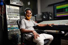 Young African-american deejay sitting in recording studio Stock Photos