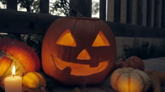 Autumnal Gourds and Candles Surround a Lit Jack o'Lantern Stock Footage