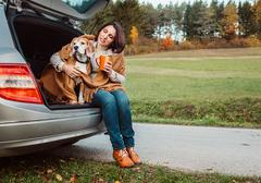Woman with dog sit together in cat truck and warms hot tea Stock Photos