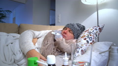Sick man wearing a warm cap and scarf in a bed coughs and measures temperature. Stock Footage