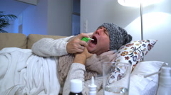 Sick man wearing a warm cap and scarf in a bed coughs and uses spray for throat. Stock Footage