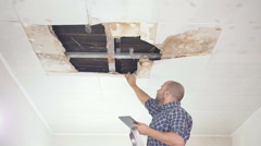 Young man makes an emergency inspection of ceiling and use Tablet PC. public Stock Footage