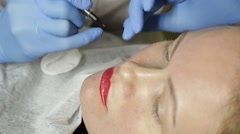 Cosmetologist applying permanent make-up. Young beautiful woman having cosmetic Stock Footage