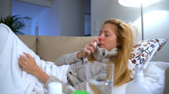 A woman with fever and runny nose uses nasal spray and sneezes. Stock Footage