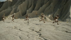 Squad of Fully Equipped and Armed Soldiers Running in  Single File in the Desert Stock Footage