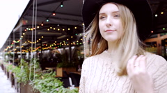 Young woman wearing hat walking near coffee house decorated with holiday lights Stock Footage