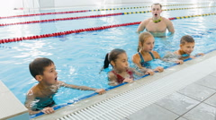 Instructor or coach and group of children doing exercises in swimming pool Stock Footage