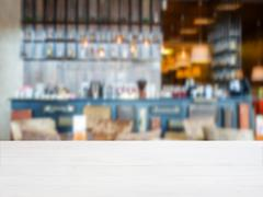 Wooden board empty table in front of blurred cafe Stock Photos