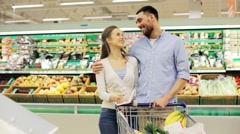Family with food in shopping cart at grocery store Stock Footage