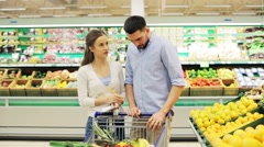 Couple with food in shopping cart at grocery store Stock Footage